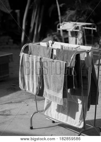 BLACK AND WHITE PHOTO OF GROUP OF TOWELS UNDER SUNLIGHT