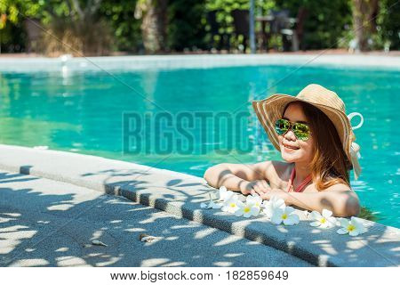 young woman with style To relax at the swimming pool in summer