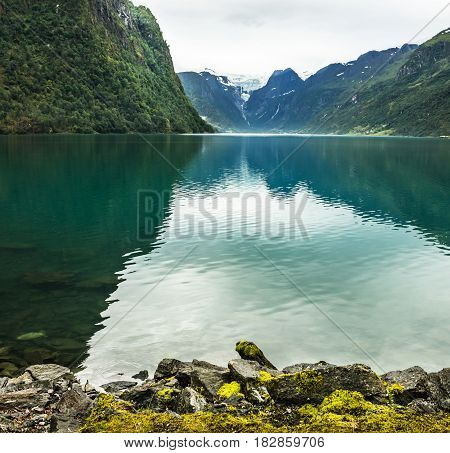 Mountain lake Oldenvatnet with the glacier Briksdal in Norway.