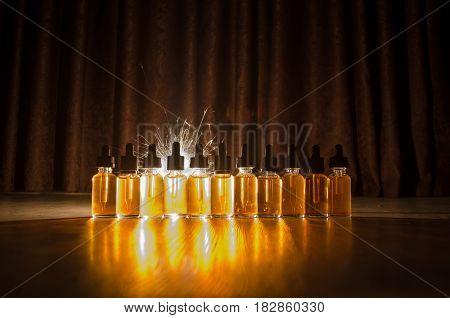 Vape Concept. Smoke Clouds And Vape Liquid Bottles On Dark Background. Light Effects.