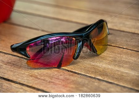 Red to yellow gradient sun glasses lying on wood table outside