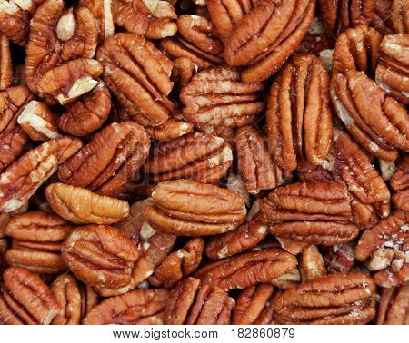 Background texture of pecan nuts showing the nuts in a natural state with perfect pecan halves and with cracked and broken ones. Space for text.