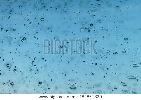 Blue blurred glass background with abstract drops