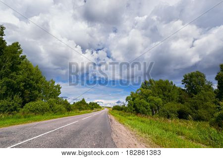 In the summer the road under Cumulus clouds, among the trees
