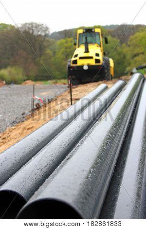 construction of a new road gravel layer and yellow street rolle pipes in foreground