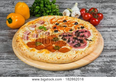 Pizza In Four Parts, With Rosemary And Spices On A Light Wooden Background. Italian Pizza On A Backg