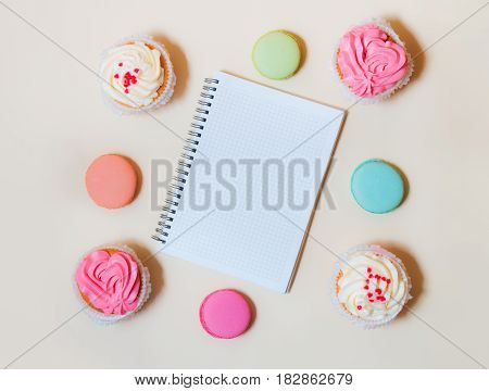 Sweet colorful macaroons cupcakes and notebook on beige background