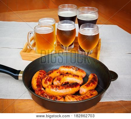 Grilled sausages and beer glasses on wooden table