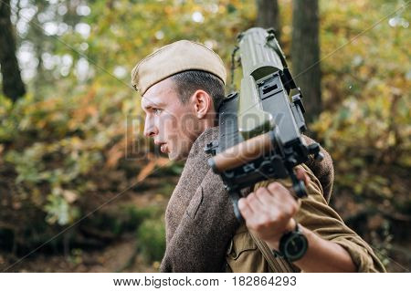 Dyatlovichi, Belarus - October 1, 2016: Young Reenactor Man Dressed As Russian Soviet Red Army Infantry Soldier Of World War II Marching In Forest With Weapon Machine-gun At Historical Reenactment