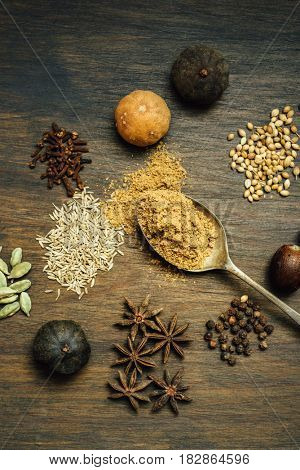 A spoonful of Baharat - an arabic mix spice along with whole spices and seeds. A rustic set up shot from from above.