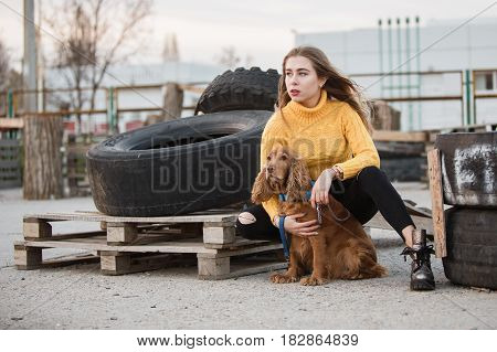 Portrait. Beautiful sexy girl, blond, young woman looking like Jennifer Aniston siting with a dog cocker spaniel, on a background of rubber wheels abandoned, wooden pallets.