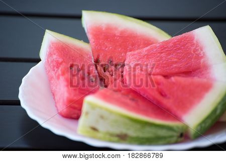 Slices of the ripe red water melon on the white plate