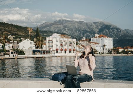 Happy Young Woman Sitting On Embankment With The Laptop. Vacations, Freelancer, Lifestyle. Successfu