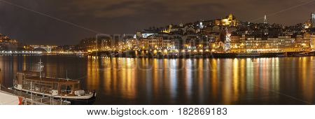 Panorama of Ribeira and Old town of Porto with mirror reflections in the Douro River at night, Portugal, Portugal.