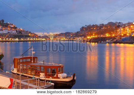 Old town of Porto with mirror reflections in the Douro River during evening blue hour, Portugal, Portugal.