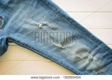lacked blue jeans on white wooden background