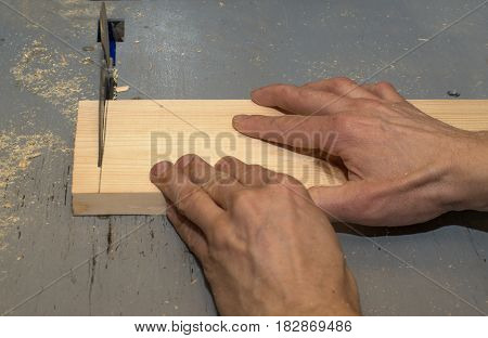 Hands holding wooden block in the disk sawing machine