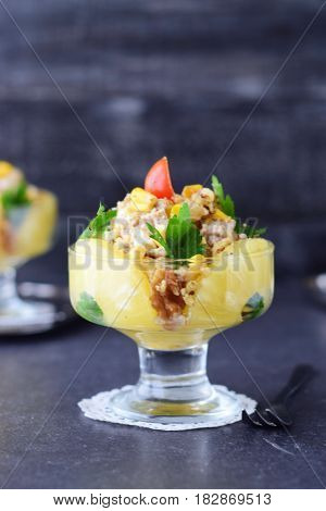 Salad with chicken fillet, pineapple, mushrooms, walnuts in a glass dish on a grey abstract background. Healthy eating concept. Russian traditional food.