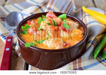Traditional Hungarian dish witth paprika and chicken in a creamy sause In a ceramic pot. Healthy eating concept