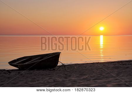 Boat silhoutte on the seashore at sunset.