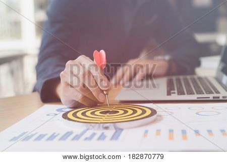 Businessman 's Hand Holding Dart Hitting At The Business Target On Dartboard On Desk In Office.  Aim