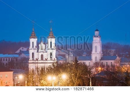 Vitebsk, Belarus. Evening Night View Of Famous Landmarks Is Church Of The Resurrection Of Christ Upper Church And Old Town Hall In Night Street Lights Illumination. Blue Hour Time