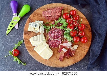 Olive wood cutting board with cherry tomatoes, arugula and variety of sliced cheeses and sausages. Snack concept