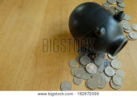 Lot of coins and black piggy bank on wood table