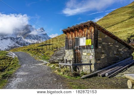 A Mountain Wooden Hut beside the road to Bachsee Switzerland in autumn with yellow grass snow and blue sky