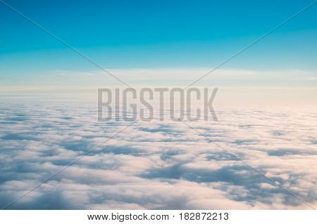 Beautiful Aerial View Of Sunny Clear Sky Over White Fluffy Clouds From Height Flight Of Plane. Bright White And Blue Colors Of Sunny Sky.