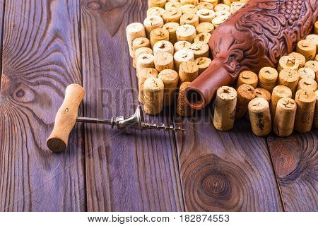 Clay bottle metal corkscrew and cork on a wooden table