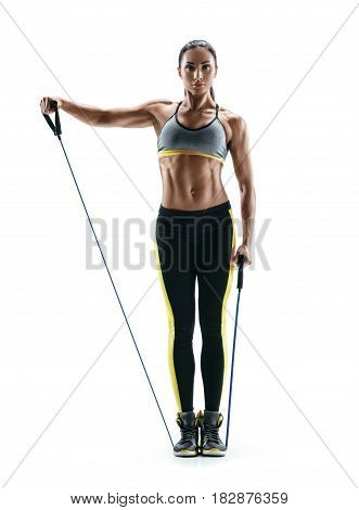 Attractive strong girl performs exercises using an resistance bands and looking at the camera. Photo of young girl isolated on white background. Strength and motivation