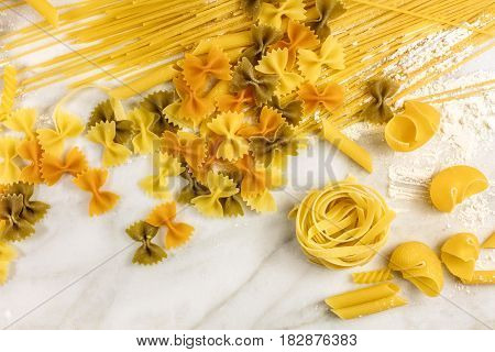An overhead photo of various types of pasta on a white marble table with flour and a place for text