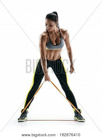 Woman with beautiful athletic body performs exercises using a resistance band. Photo of young woman isolated on white background. Strength and motivation.
