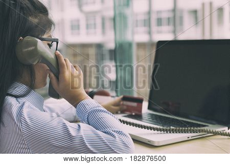 Young Asian Girl Holding Credit Card, Making Call, Using Telephone, Talking On Phone And Using Lapto