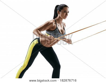 Beautiful athletic woman during workout with suspension straps. Young woman performs fitness exercises on white background. Strength and motivation