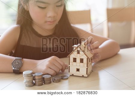 Little Asian Girl Hold Little House With Money Stack - Money Saving Education Concept