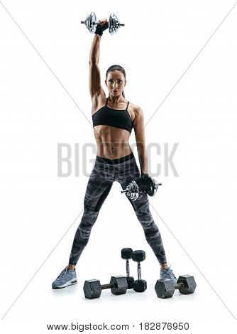 Strong muscular girl doing exercises with heavys dumbbells. Photo of attractive brunette isolated on white background. Strength and motivation.