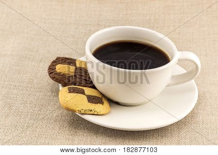 Cup of coffee with biscuit chess like cookies on burlap sackcloth background. Coffee break breakfast.