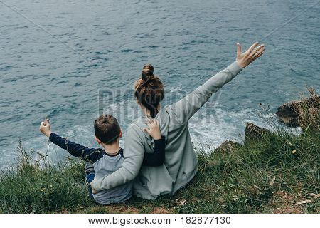 Back View Of Woman And Her Son Raised Their Hands Upwards Sitting On The Mountain Above The Sea. Fre