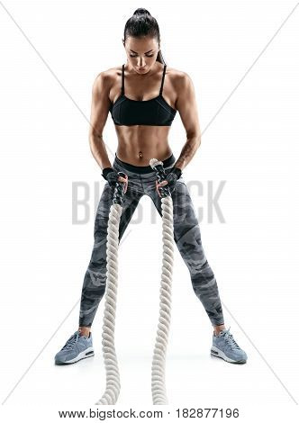 A strong woman is preparing to work with heavy ropes. Photo of attractive woman in sportswear isolated on white background. Strength and motivation.