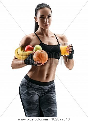 Beautiful athletic young woman with fresh fruits and orange juice posing on white background. Organic food and health concept