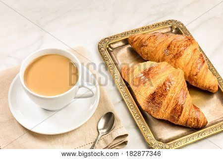 A photo of a cup of coffee with fresh croissants, with a place for text