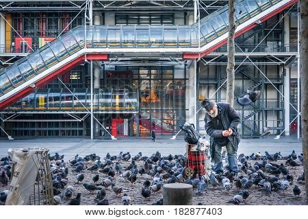 PARIS - January 4 2016: Unidentified elderly man feeding pigeons in front of Pompidou Centre in Paris France.