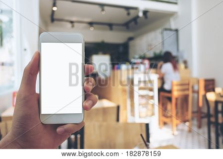 Mockup image of hand holding mobile phone with blank white screen in wooden cafe