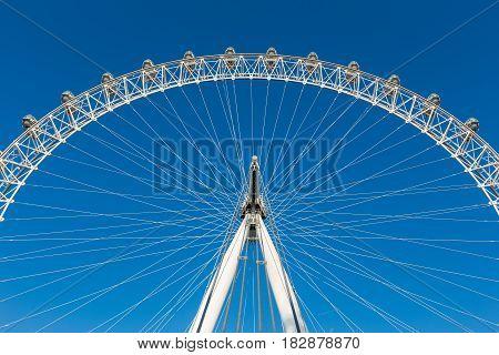 section of London Eye ferris wheel in London against clear blue sky