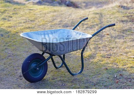 Empty wheelbarrow in metal color, grass in the background