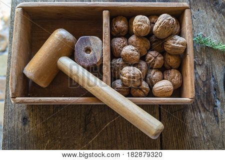 Top view of traditional wooden hammer beats walnuts on the wooden table