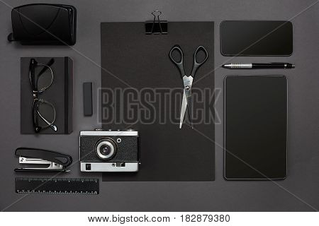 Workplace with office items and business elements on a black background. Concept for branding. Top view. Copy space. Still life