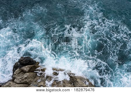 Danger sea wave crashing on rock coast with spray and foam before storm in Positano Italy